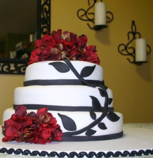 red flowers, black vines, white fondant wedding cake