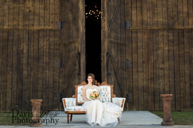 A bride poses in an antique couch in front the Barn at Water Oaks wedding venue.