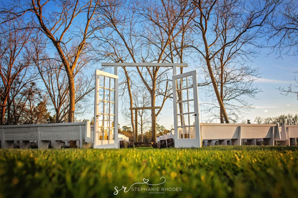white pews outdoor wedding venue